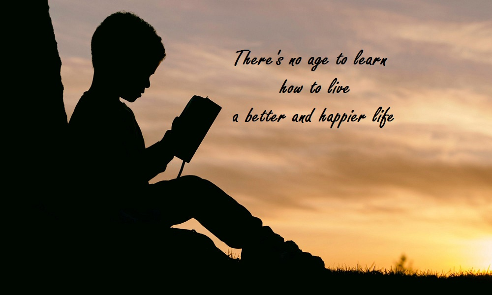 Image shows a child reading a book. The message is there is no age to learn how to live an enhanced life.
